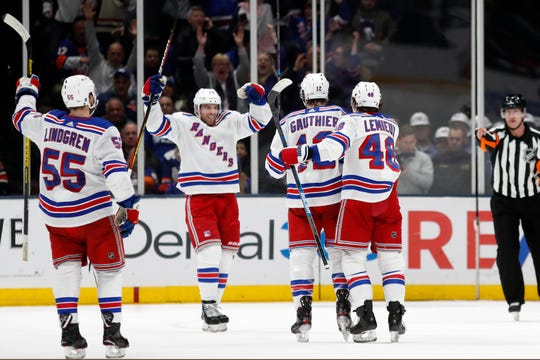 New York Rangers center Greg McKegg, second from left, celebrates with teammates after scoring a goal during the second period of an NHL hockey game against the New York Islanders, Tuesday, Feb. 25, 2020, in Uniondale, N.Y. Also shown are Rangers defenseman Ryan Lindgren (55), right wing Julien Gauthier (12) and left wing Brendan Lemieux (48). (AP Photo/Kathy Willens)