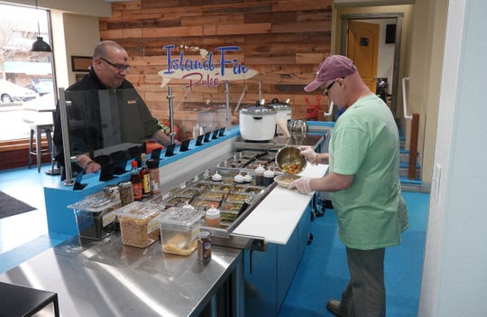 (left to right)Customer Jack Russell builds a bowl of island flavors at the new Island Fin Poke on Delaware Avenue in Trolley Square that opened for business on Monday. Donnie Hatfield prepares the bowl.