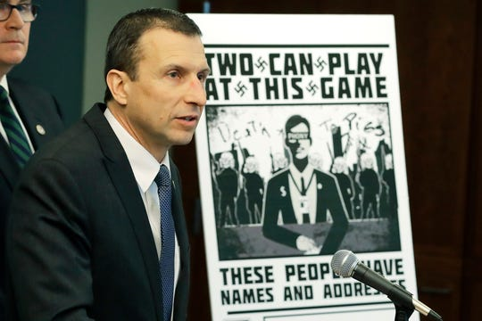 Raymond Duda, FBI Special Agent in Charge in Seattle, speaks Wednesday, as he stands next to a poster that was mailed earlier in the year to the home of Chris Ingalls, an investigative reporter with KING-TV during a news conference in Seattle. Officials charged a group of alleged members of the neo-Nazi group Atomwaffen Division for cyber-stalking and mailing threatening communications — including Swastika-laden posters — in a campaign against journalists in several cities.
