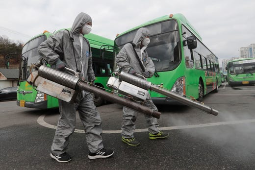 Workers wearing protective suits spray disinfectant as a precaution against the coronavirus at a bus garage in Seoul, South Korea, Feb. 26, 2020. The number of new virus infections in South Korea jumped again Wednesday and the U.S. military reported its first case among its soldiers based in the Asian country, with his case and many others connected to a southeastern city with an illness cluster.