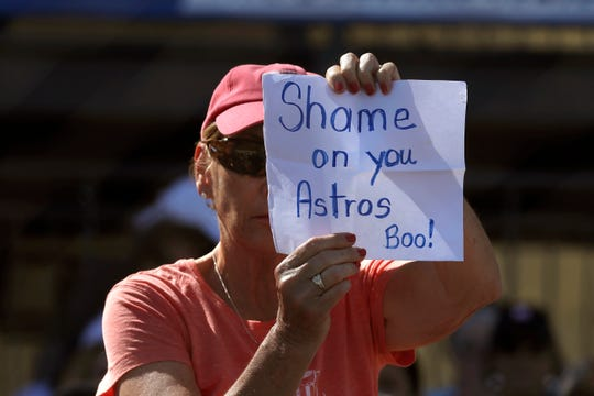 A fan holds shows her displeasure with the Astros during a spring training game.