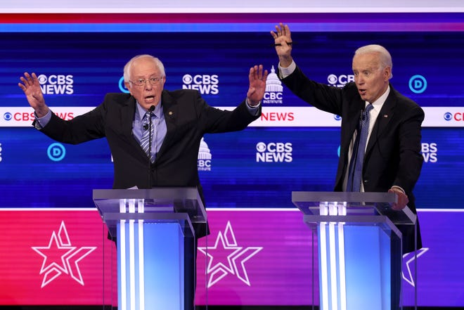 Democratic presidential candidate Sen. Bernie Sanders speaks as former Vice President Joe Biden reacts during the Democratic presidential primary debate.
