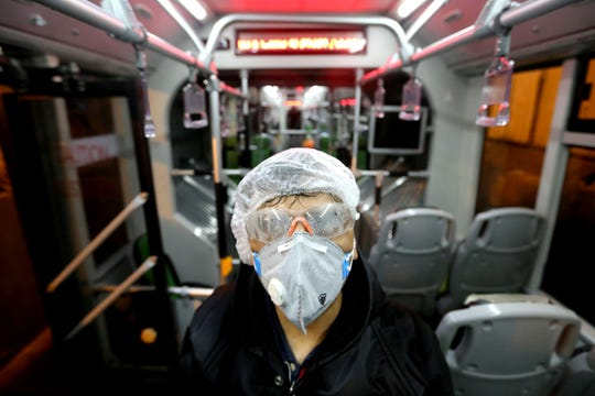A Tehran municipality worker cleans a bus to avoid the spread of the COVID-19 illness on Feb. 26.