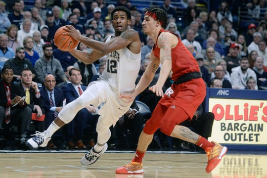 Penn State's Izaiah Brockington (12) drives to the basket past Rutgers Caleb McConnell,right, during the first half of an NCAA college basketball game, Wednesday, Feb. 26, 2020, in State College, Pa.