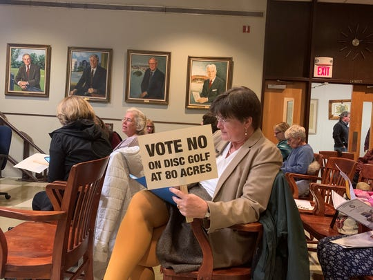 Monmouth University Environmental Science Professor Catherine Duckett holds a sign against disc golf at Leon Smock 80 Acres Park at a Eatontown Mayor and Council meeting Feb. 27, 2020.