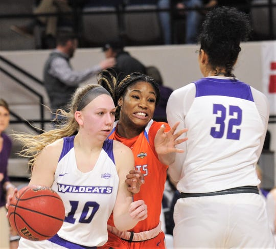 Sam Houston State's Courtney Cleveland, center, squeezes between a pick set by ACU's Makayla Mabry (32) as she chases Breanna Wright in the second half.