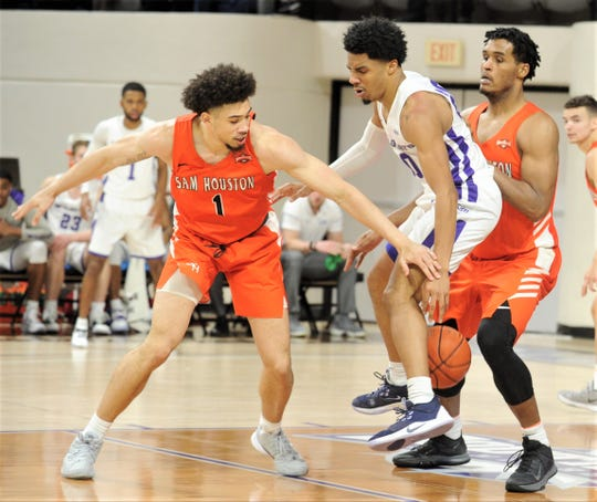 ACU's Coryon Mason, center, knocks the ball away from Sam Houston State's R.J. Smith in the first half. ACU beat the Bearkats 85-69 in the Southland Conference game Wednesday, Feb. 26, 2020, at Moody Coliseum.