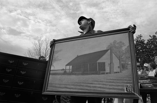 The image of an auctioneer shouting during an estate auction in Bishopville, S.C., exemplifies the gradual decline of small farms across the country.