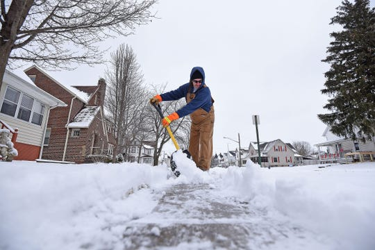 Dave Frontz clears the sidewalk Thursday afternoon in front of his home on North Wiley Street in Crestline.