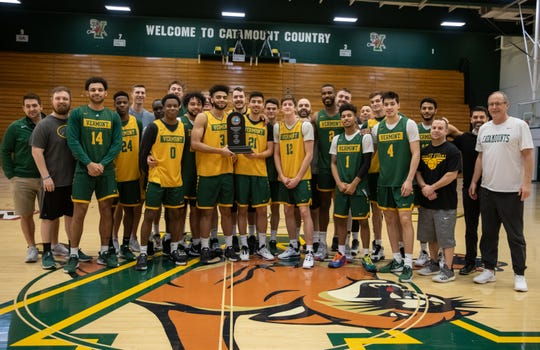 The UVM men's basketball team poses with the America East regular-season championship trophy prior to Thursday's practice. The Catamounts won the league's regular-season crown for a record fourth straight season.