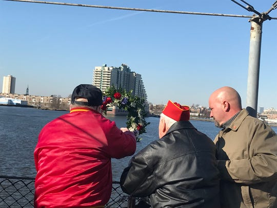 Former Marine Corps veterans  from Camden County,  Frank Beach, left, and John Welsh, center, toss a memorial wreath into the Delaware River in Camden from the Battleship New Jersey museum ship to remember the nearly 7,000 Marines who died in the Battle of Iwo Jima during world War. The two men fought in the five-week battle, whose 75 anniversary is commemorated from Feb. 19 to March 26.