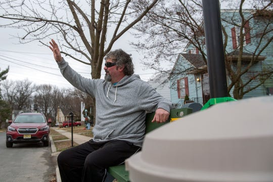 """Greg """"Big Daddy"""" Conklin waves to a friend from his bench in front of his home in Gloucester City."""