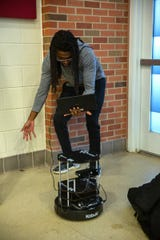 Isaiah Carmichael measures the robot's computer vision depth at a recent Robotics II class.