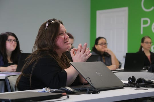 Digital Works graduate Jessica Romey speaks with a staff member at Digital Works, a new nonprofit dedicated to helping military spouses find telework jobs.