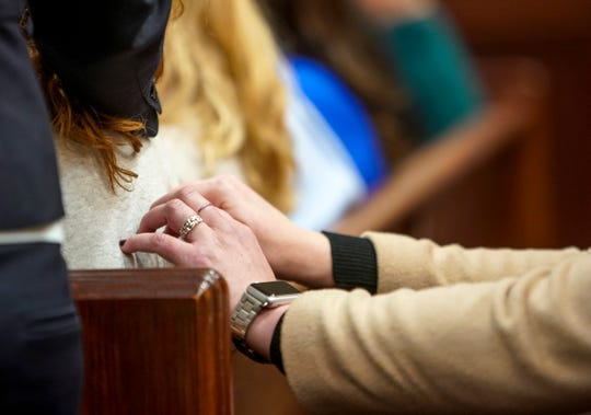 A family member places hands in support onto the back of Jami Carlson, the mother of Allison Tenbarge, at the Montgomery County Courthouse in Clarksville, Tenn., on Feb. 26, 2020.