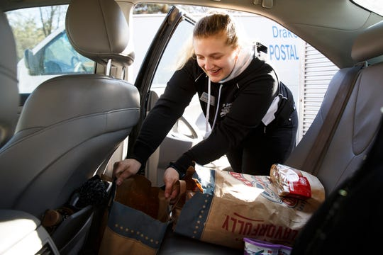 Drake sophomore Ashly Frazier puts food into Aspen Walters' car before they deliver it to Children and Family Urban Movement on Wednesday, Feb. 26, 2020, in Des Moines. Walters and Frazier are part of Next Course, a food recovery program that takes leftover food from the campus dining halls to local shelters that can redistribute it.