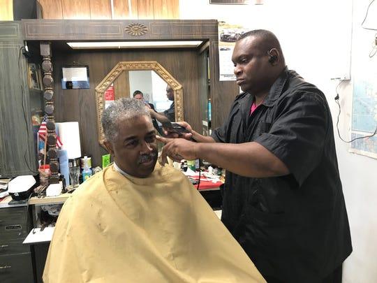Bryan James cuts hair of Ray Foxworth, Sr.