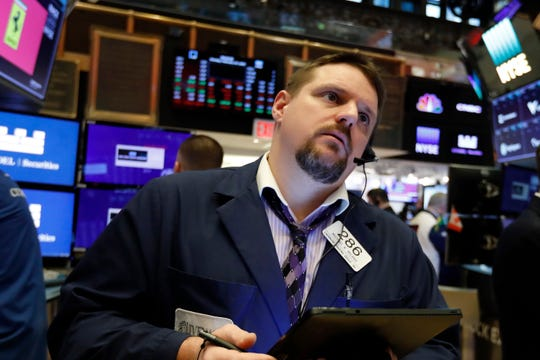 Stocks fell more than 950 points in trading on the morning of Feb. 27, as investors tried to judge the impact of coronavirus on corporate earnings. FILE - On Feb. 24, 2020, trader Michael Milano works on the floor of the New York Stock Exchange. (AP Photo/Richard Drew, File)