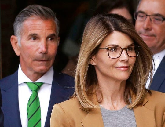 In this April 3, 2019, file photo, actress Lori Loughlin, front, and her husband, clothing designer Mossimo Giannulli depart federal court in Boston. Lawyers for Loughlin and Giannulli said Wednesday, Feb. 26, 2020 that new evidence shows the couple is innocent of charges that they bribed their daughters' way into the University of Southern California.