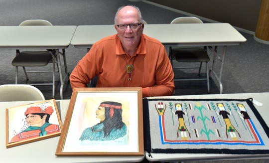 Jim Haverland with two Seminole portraits and a Navajo rug.