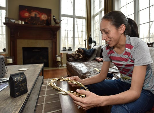 At her home in Rochester, Des Linden holds the laurel wreath from her win in the Boston Marathon.