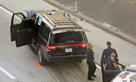 Los Angeles police officers stand after a pursuit of a stolen hearse with with a casket and body inside on Interstate 110 in South Los Angeles Thursday, Feb. 27, 2020.  The hearse was stolen from outside a Greek Orthodox church in East Pasadena on Wednesday night. The Los Angeles County Sheriff's Department says one person is in custody.