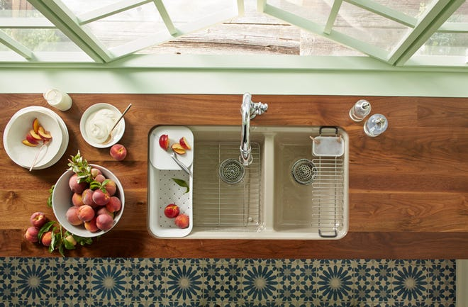 A large/medium double-bowl sink gives one oversized bowl for dishes and one smaller bowl dedicated to the disposal.  (Kohler/TNS)