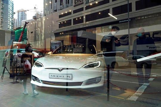 A staff member talks to a man inside a Tesla store in Hong Kong, Thursday, Feb. 20, 2020.