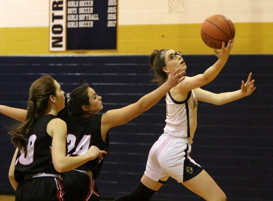 Maddy Watts of Elmira Notre Dame goes up for a layup as Oxford's Ellie Ryan (24) and Olivia Kelsey (10) defend during Oxford's 60-57 win in the first round of the Section 4 Class C girls basketball tournament Feb. 26, 2020.