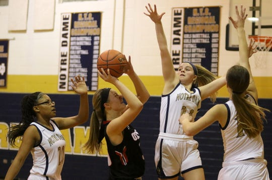 Oxford's Karley Miller goes up for a shot in between Elmira Notre Dame's Kahlia Rivera (20), Taylor VanDine (center) and Shannon Maloney (right) during Oxford's 60-57 win in the first round of the Section 4 Class C girls basketball tournament Feb. 26, 2020.