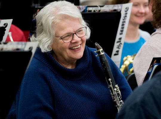 Marcia Wines laughs after band director Jerry Reese makes a joke during an Old Dam Community Band rehearsal at Castle South Middle School in Newburgh, Ind., Tuesday evening, Feb. 25, 2020.