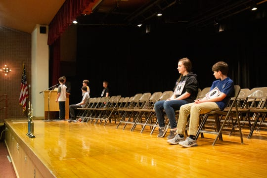 Nora McKelvey and Conner Sturges of Holy Spirit Catholic School watch as four students compete for third place at the 2020 Cascade County Spelling Bee.