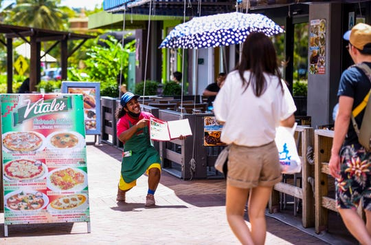 Vitale's Ristorante Italiano employee Renhared Shimi, rises to his feet after playfully attempting to persuade passing tourists into the Tumon eaterie on Thursday, Feb. 27, 2020.