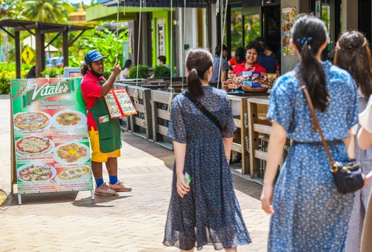 Vitale's Ristorante Italiano employee Renhared Shimi, left, and Beachin' Shrimp hostess Micah Mac attempt to persuade passing tourists in to visiting their eateries in Tumon on Thursday, Feb. 27, 2020.
