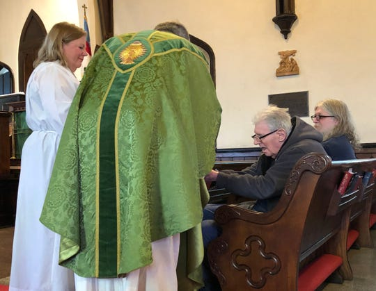 Fr. Robert Alves serves Holy Communion on Feb. 16 with 97-year-old Brod Seymour, the oldest member of St. Paul's Episcopal Church.