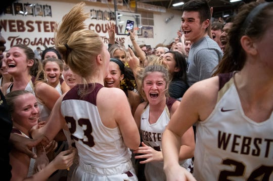 Webster County celebrates with the student body on the floor after beating Henderson County for their fourth-straight district championship at Webster High School in Dixon, Ky., Wednesday night.