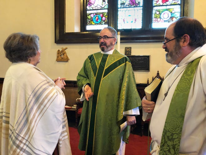 Fr. Robert Alves, center, greets St. Paul's Episcopal Church congregant Carol Noon following the 10 a.m. worship service on Feb. 16, as St. Paul's rector Fr. Rich Martindale looks on.