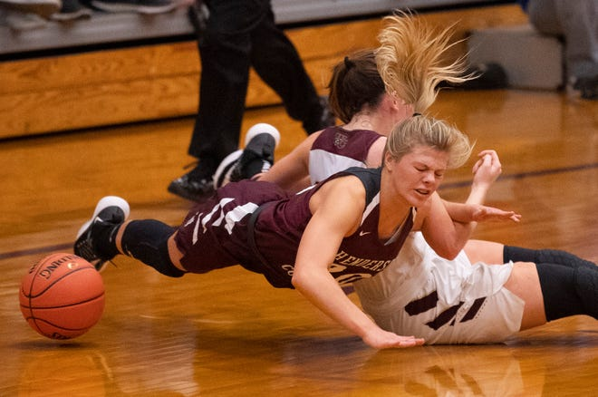 Henderson County's Kaytlan Kemp (20) and Webster County's Adeline McDyer (24) fight for the ball during the Sixth District Tournament girls finals at Webster High School in Dixon, Ky., Wednesday night.