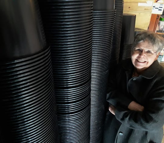 Pat Fish stands next to 2,000 black plastic 3-gallon flower pots stacked high in her North Liberty garage. She collects them from Costco and works hard to find innovative ways to recycle or re-purpose them.