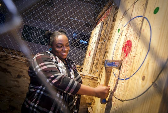 Phoebe Segal, of Pearl, happy with her throw, retrieves her ax from the target while throwing at Black Axes Throwing Club on Old Fannin Road in Brandon Wednesday, Feb. 26, 2020.