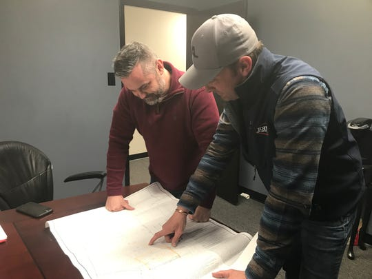 Brandon Buchanan (left) and Josh LeFevre look over layout plans for the proposed Grace Cove Apartments in Medina.