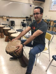 José Ramos teaches instrumental music to the entire student body at Beaumont Magnet Academy, starting with the correct way to handle the instruments. Here, he demonstrates the proper protocol for getting a drum into playing position. Sept. 24, 2019.