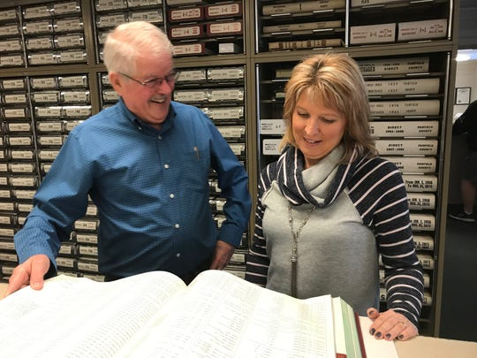 Fairfield County Recorder Gene Wood (right) examines a record book with employee Lisa McKenzie in this Eagle-Gazette file photo from February. Wood is retiring after 45 years in the office and Tuesday was his last day on the job. McKenzie ran unopposed the recent primary election to replace Wood.