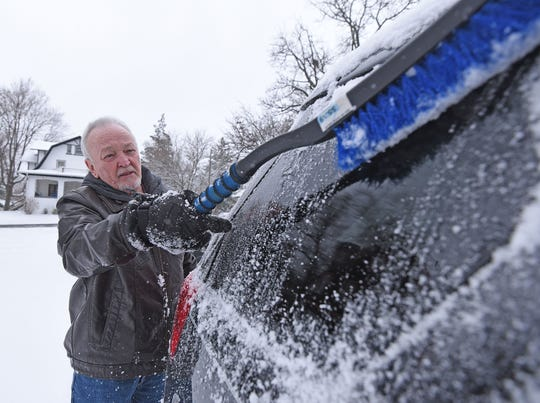 Steve Stephenson cleans the snow off his car Thursday morning after a heavy snowfall overnight.
