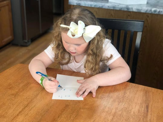 Allison Krueger, 6, writes a card for the victims of the Molson Coors shooting.