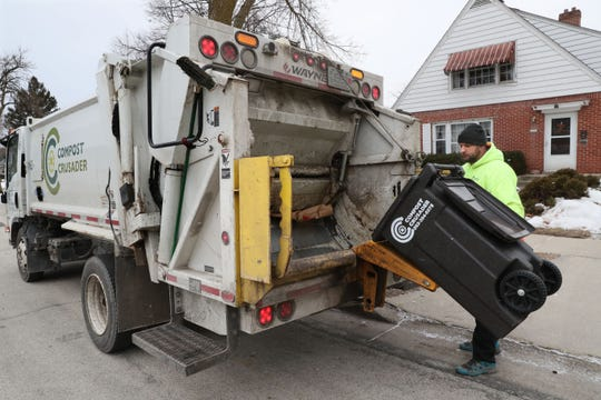 Compost Crusader driver Robert Johnson makes a pickup in a residential area of Wauwatosa, emptying compost containers into his truck. Compost Crusader, a St. Francis-based composting company, is hoping to be a part of the DNC's composting efforts. The company works with several municipalities and businesses diverting 2.8 million pounds of waste in 2019.