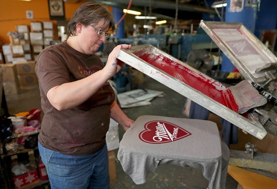 """Susan Ullenberg, a screen printer for Brew City Brand, works on screen printing """"Miller Strong"""" shirts Thursday at the company on Milwaukee Street in the Third Ward. In one of the worst shootings in Wisconsin history, a gunman killed five people and then himself Wednesday afternoon on the Milwaukee campus of Molson Coors."""