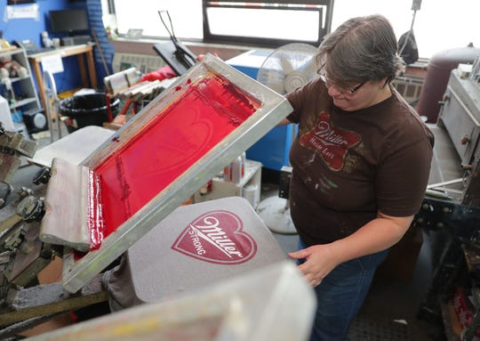 "Susan Ullenberg, a screen printer for Brew City Brand, works on a ""Miller Strong"" shirt at the company in Milwaukee's Third Ward Thursday."