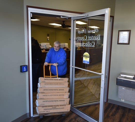 Jerry Brown of MailCo USA wheels out trays filled 2019 property tax statements Thursday at the Baxter County Collector's Office. The county will mail or email almost 32,000 statements this year.