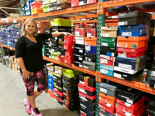 Darla Atkins shows off the large shelves of shoes in the warehouse where the big blowout shoe sale will be this weekend.
